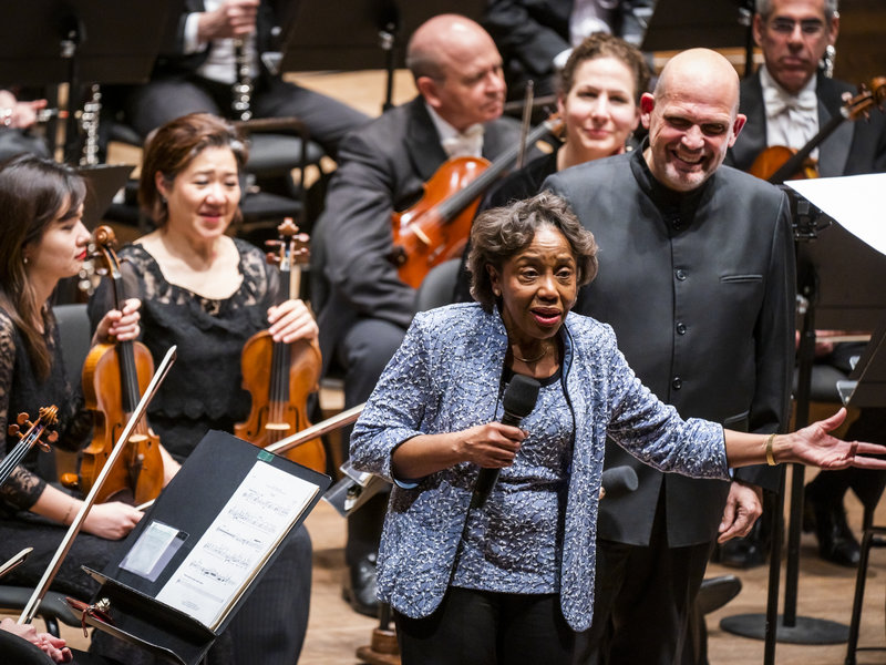 """2020Feb_ICYMI_NPR; Tania León speaks at the premiere of her piece """"Stride,"""" one of 19 pieces composed by women that the New York Philharmonic commissioned to celebrate the 100th anniversary of the 19th Amendment. Chris Lee/Courtesy New York Philharmonic"""